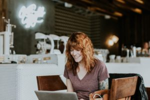 avoiding pop up ads makes a better user experience - woman sitting at computer smiling